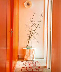 Steal this idea! Orange hallways and hand-painted hop scotch art.
