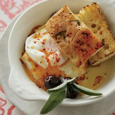 Poached Eggs with Baked Feta and Olives - The combination of toasted bread, poached eggs, sizzling feta and olives is so delicious, it is great for breakfast, lunch or dinner.  http://www.foodandwine.com/recipes/poached-eggs-baked-feta-and-olives