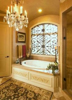 My next house is going to have a garden tub and hopefully a gorgeous window like this. Not completely sold on the chandelier though... maybe if it was black. And the room was a bit less yellow, but darker and bolder, more red.