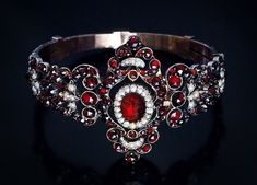 An ExquisiteVictorian Era Renaissance Revival Antique Garnet Bracelet    of an elaborate openwork design, centered with an oval cabochon garnet (carbuncle) within seed pearl surrounding.     The bracelet is hand crafted in silver and completely covered with rose-cut glowing red Bohemian (pyrope) garnets highlighted with seed pearl scrolls and trefoils.    circa 1870