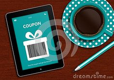 Tablet with discount coupon and  cup of coffee lying on wooden desk