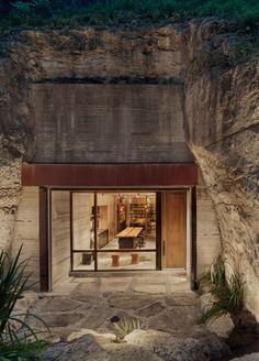 Située à l'extrémité Est de la région de Texas Hill Country aux États-Unis, cette cave à vin privée est littéralement intégrée dans une colline calcaire, disparaissant presque dans son environnement naturel. La cour d'entrée sans prétention révèle partiellement l'espace l'intérieur, encore camouflé par des rochers calcaires, recueillis lors de l'excavation, et une végétation luxuriante. L'ouverture extérieure de la grotte est coiffée d'un portail en béton banché, destiné à s'altérer...