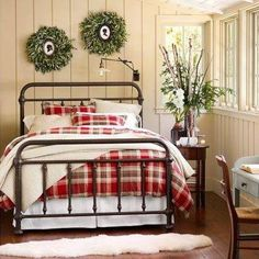 Cozy bedroom cream board/batten walls, divided light windows, brown/red plaid duvet with brown iron bed...nice!