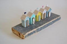 Miniature beach huts handmade from driftwood and reclaimed materials. In seaside blues, whites and yellow these little huts have lovely little distressed flaky paint doors. All painted driftwood is as found including the piece of dark grey driftwood that they are mounted on. The huts measure approx. 5 cm tall. The whole piece measures approx. 8 cm tall, 25 cm long and 8.5 cm deep. Would make a fab display piece in any style of home.   I would advise not displaying this piece in a…