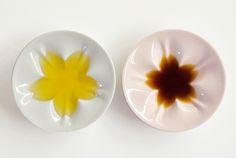一見すると不思議な凹凸のある小皿。そこへしょうゆを差してみると、思いのほかくっきりと愛らしい桜が浮かび上がります。 こちらは「hiracle(ヒラクル)」と名づけられた九谷焼の桜小皿。 置物の制作などで培われた、造形的に高い技術を持つ窯元と、金沢を拠点に活動するデザイン事務所「エイジデザイン」のコラボレーションで生まれ...