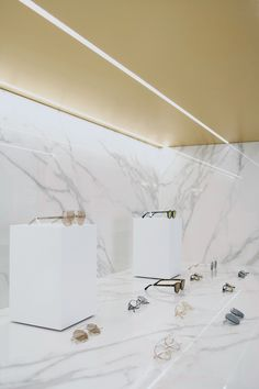 Luxury modern eyewear retail store by Lunetterie Générale. Shop in shop concept store with brass panels & calacatta marble effect Neolith. Custom museum style pedestals. Limited eyewear brands.