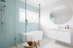 Powder blue herringbone subway tile feature wall in this modern coastal bathroom. Adore the natural materials in this space to soften the look too.