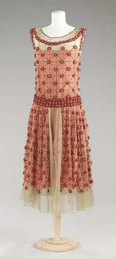 Jeanne Lanvin, 1923. Evening Dress. Front view. White tulle, overall pink ombré ribbonwork embroidery, rosettes in modified latticework pattern; pink crepe de chine a. Dress: Tubular; mid-calf length; dropped-waist bodice; sleeveless; bateau neck; skirt gathered at waistband; CF opening on skirt b. Slip: Pink crepe de chine; tubular; sleeveless; square neck