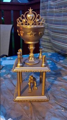 DIY trophy for family game night. Pieces from Goodwill and various other places (bowl, candle stick, plastic tiara, plastic beaded necklace, game pieces, small toys, stickers; wood pieces for bases and support from Michaels) all spray painted gold and glued together.