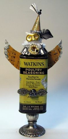 Altered Art - made with Poultry tin, tart tin, Avon cat perfume bottle head, candle stick, junk, handmade wings from vintage music, handmade hat, brass mask  #AlteredArt #foundObjectArt Found Object Art, Assemblages, Assemblage Art, Fat Cats, Vintage Music, Candlesticks, Mardi Gras, Altered Art, Poultry