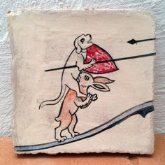 Medieval jousting dog on hare thick handmade glazed ceramic tile. Hand-painted figure from medieval illuminated manuscript.