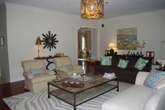 Living Room - zebra patterned rug, custom made throw pillows, gold leafed chandelier, rustic wood coffee table