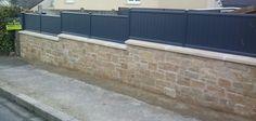 Dans le centre ville de Trégueux, Mur en granit gris beige avec couvertine et palissades pleines en Aluminium