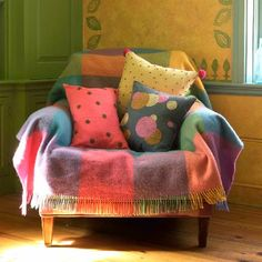 Chair with throw and pillows, love the colors and textures... from the Kristin Nicholas blog Getting Stitched on the Farm