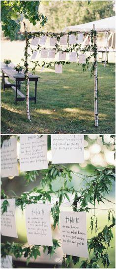 Escort card display, birch tree branches, greenery vines, black calligraphy // Eric Kelley