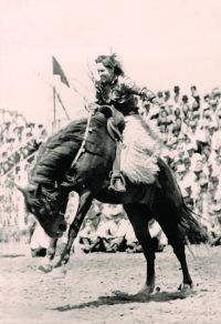 Tad Lucas (1902-1990) grits her teeth on a saddle bronc during a women's bronc riding exhibition.