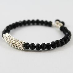 - Product Info - Product Care - Shipping This memory wire bangle bracelet is so simple yet so pretty! 6mm shiny black faceted crystal beads are strung with one set of silver tone spacers on a memory w