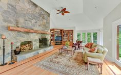 Family room with dramatic fireplace and doors out to a large sun deck with views of the river, BRLA trails and bordering St-Matthews preserve. in Bedford, NY. Saint Matthew, Residential Real Estate, Luxury Real Estate, Palm Beach, The Hamptons, St Matthews, Family Room, Living Spaces, Preserve