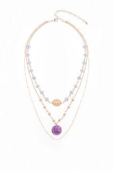 Collar de 42cm de largo y 8cm de extensión, en baño de oro con cuenta color morado tornasol, piedra color durazno y color morado.  Collar modelo317513