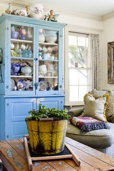 Some may have opted to paint over the bright blue color of this china cabinet (which once lived in an old barn) but Amanda went a different route. Instead, she uses it to store antique collectables—many of which have blue details.