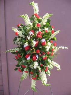 Stand #4    Similar flowers sell for 125.00    A wonderfully traditional red and white standing spray of snapdragons, larkspur, mini carnations and hypericum. We've added red and white ribbon loops to emphasize this color combination. Truly a favorite.