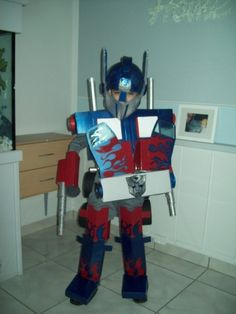 Transformer Optimus Prime costume: paper mache head, paper tubes, the body is cardboard boxes from various products, gray clothing underneath  Halloween