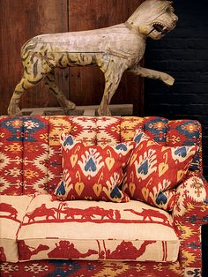 Andrew Martin - Discovery Plain Fabric Collection - Sofa with dark red and blue Aztec-like pattern with seat cushions in pale sandy colour, depicting dark red camel-like creatures. Orange And Purple, Red And Blue, Dark Red, Bohemian House, Unique Wallpaper, Moroccan Design, Roman Blinds, Unique Furniture, Surface Pattern