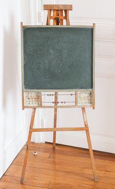 Ancien tableau d'écolier vintage en bois avec boulier, abécédaire et chiffres sur papier.
