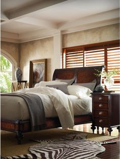 The handsome panel molding and rich tones of this bed are perfectly English, while a zebra skin rug and Chinese pottery add an exotic flare.