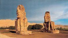 Colosos del templo de Amenophis III, XVIII Din., Kom-el Hetan, Tebas. Las estatuas muestran las dimensiones que llegó a tener el templo. Dedicado a Amón y al faraón, tenía 3 pares de pilonos precedidos por estatuas de faraón que eran progresivamente más pequeñas acentuando el efecto de prespectiva. Se llegaba a una larga estancia que servía de camino procesional, daba a un gran patio solar y de aquí al santuario. Un muro lo protegía de las inundaciones a modo de colina primigenia.