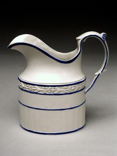 """English Castleford-type white feldspathic stoneware, oval cream jug shaped with molded and applied relief decoration and blue trim, and impressed on the base """"24"""". The Castleford Pottery was run by David Dunderdale & Co., operating from 1790 to 1821 in Castleford, about 15 miles from Leeds in Yorkshire;"""