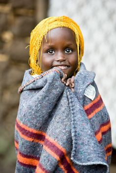 A sponsored girl hugs a blanket in her village outside Kampala