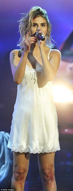 A cut above: Selena emerged with 'cuts' on her knees and forehead as she rocked a white mini nightgown