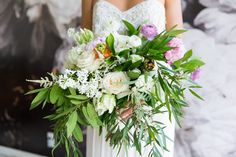 Bride in a sleeveless beaded two piece wedding gown holding a green pink and white large bridal bouquet by The Flower Shop, photo by Cavin Elizabeth Photography