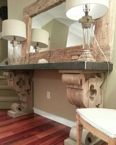 For this entry table, I took reclaimed barn beams and cut and carved them out to mimic the look of old corbels. The top is raw steel and the mirror is created using the outside cuts of centuries old barn beams.