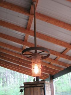 """Hanging light for my outdoor kitchen..  Materials used:  Front wheel off old plow; mesh wire gutterguard; old barbed wire; vintage measuring cup; pvc piped covered with """"rusted"""" effect paint; threaded rods, nuts, washers etc... I am so pleased with the end result! One down, one to go!!"""