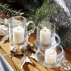 Holiday Decor that Lasts from Thanksgiving to Christmas: Clearly Beautiful- Use different-shape clear glass pitchers as candleholders for a sparkling display. Here, a trio of pitchers with beeswax votive candles make the mantel twinkle.