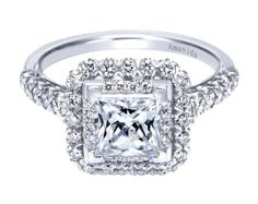 It's hip to be square. So stay in style and have a stunning square shaped center stone for your perfect engagement ring! This is a beautiful 18k White Gold Contemporary Halo Engagement Ring by Gabriel & Co. This special ring has many little diamonds surrounding a flawless center stone!