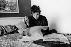 Bob Dylan reading the newspaper on a hotel bed, Philadelphia, Pa., 1964.  On the fiftieth anniversary of Bob Dylan's first album release, photographer Daniel Kramer talks to LightBox about working with Dylan at an early and pivotal point in the troubadour's musical career.