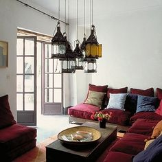 I want to do this! I already have 1 lantern' I just need a few more! //A sea of fantastic Moroccan lanterns hangs down in this cozy living room.
