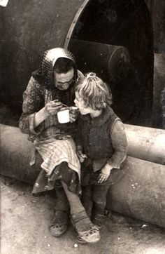 Lodz, Poland, A woman feeding a child in the ghetto.