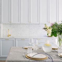 Ljusgrått kök med carraramarmor och mässing