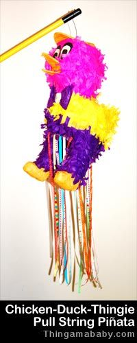 Photo of a chicken or duck-like pinata suspended from a broom handle as many strings dangle between the animal's legs.