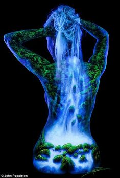 Photographer John Poppleton paints a model's hair so that the waterfall scene etched onto her back appears to begin at the top of her head