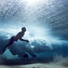 Underwater photo, swimmers under a wave. Murray Mitchell.