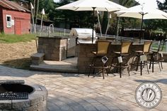 An outdoor kitchen in New Jersey with a paver patio by Barrett Outdoors.