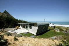 The design for the form of the building, a simplified abstraction of the form of a caravan, conceives of the bach as a kind of aerofoil or ship's hull protecting the inhabitants from the prevailing north-west winds sweeping down from the hills behind. Green Architecture, Architecture Design, New Zealand, Coastal, Environment, Train, Explore, Landscape, Studio