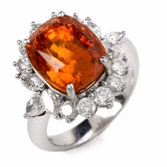 This enchanting GIA Certified floral motif diamond sapphire ring is crafted in solid platinum, weighing approx: 15.04 grams and measuring 21mm x 19.5mm. Designed with a spectacular center stone, GIA Certified (Report # 5172374743), genuine oval cushion cut, transparent orange sapphire weighing approx 10.32cts in a prong setting and measuring approx: 12.54 x 10.02 x 9.50mm. This breathtaking halo sapphire ring surrounded by 6 genuine marquise cut diamonds, clarity and 10 genuine round cut…