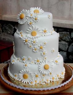Delightful three tier round white wedding cake covered with small and large intricate white hand made fondant dasies with a yellow centre. From sweetobsessions www.flickr.com