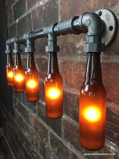 The Brewers Vanity Light is an industrial piece perfect for lighting up your bar or man cave bathroom. The lamp is versatile and works as a decorative sconce or sitting above your vanity. The sconce is constructed from authentic black iron piping. The bottles are firmly secured in the black iron coupling without causing damage. A 25 watt bulb is used to illuminate the beer bottles producing a warm ambient light. Each bottle is sandblasted in order to diffuse the light evenly throughout the…